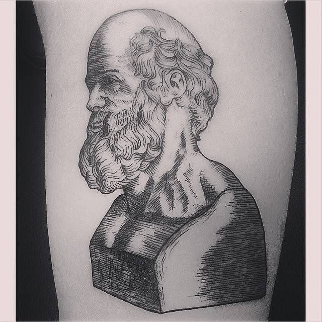 Woodcut style Hippocrate bust tattoo on the left upper arm.
