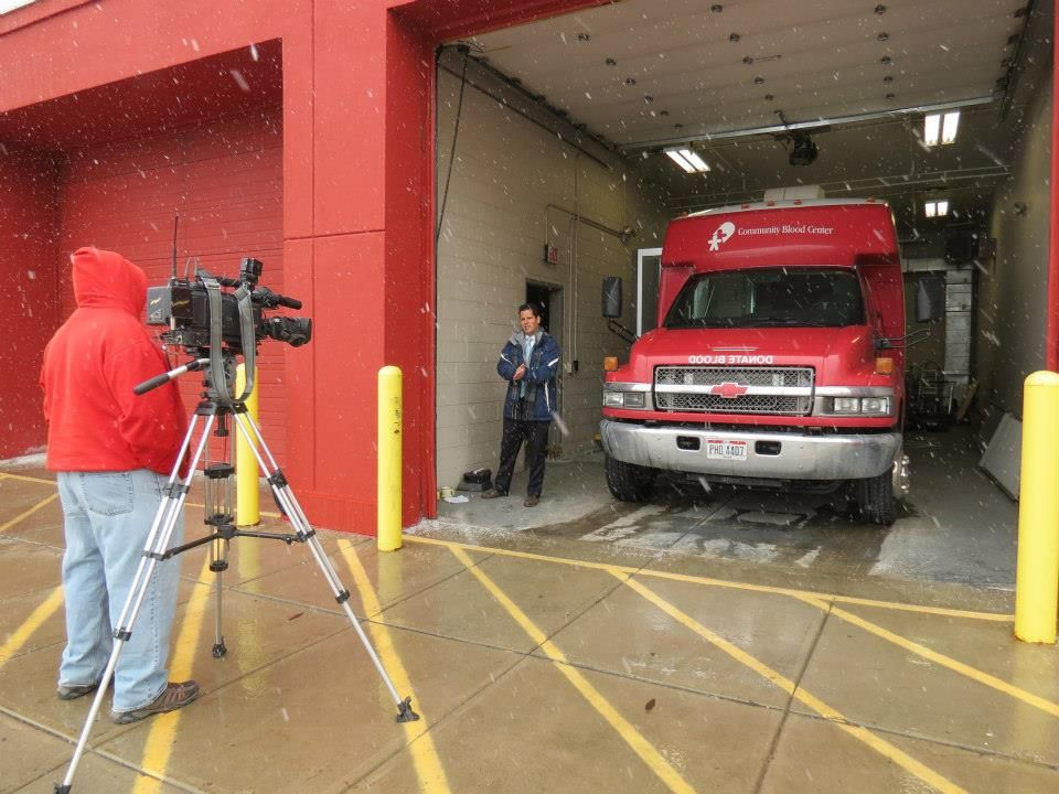 Snowflakes fly as Glenn tapes part of his report from the Bloodmobile garage bay. — at Community Blood Center.