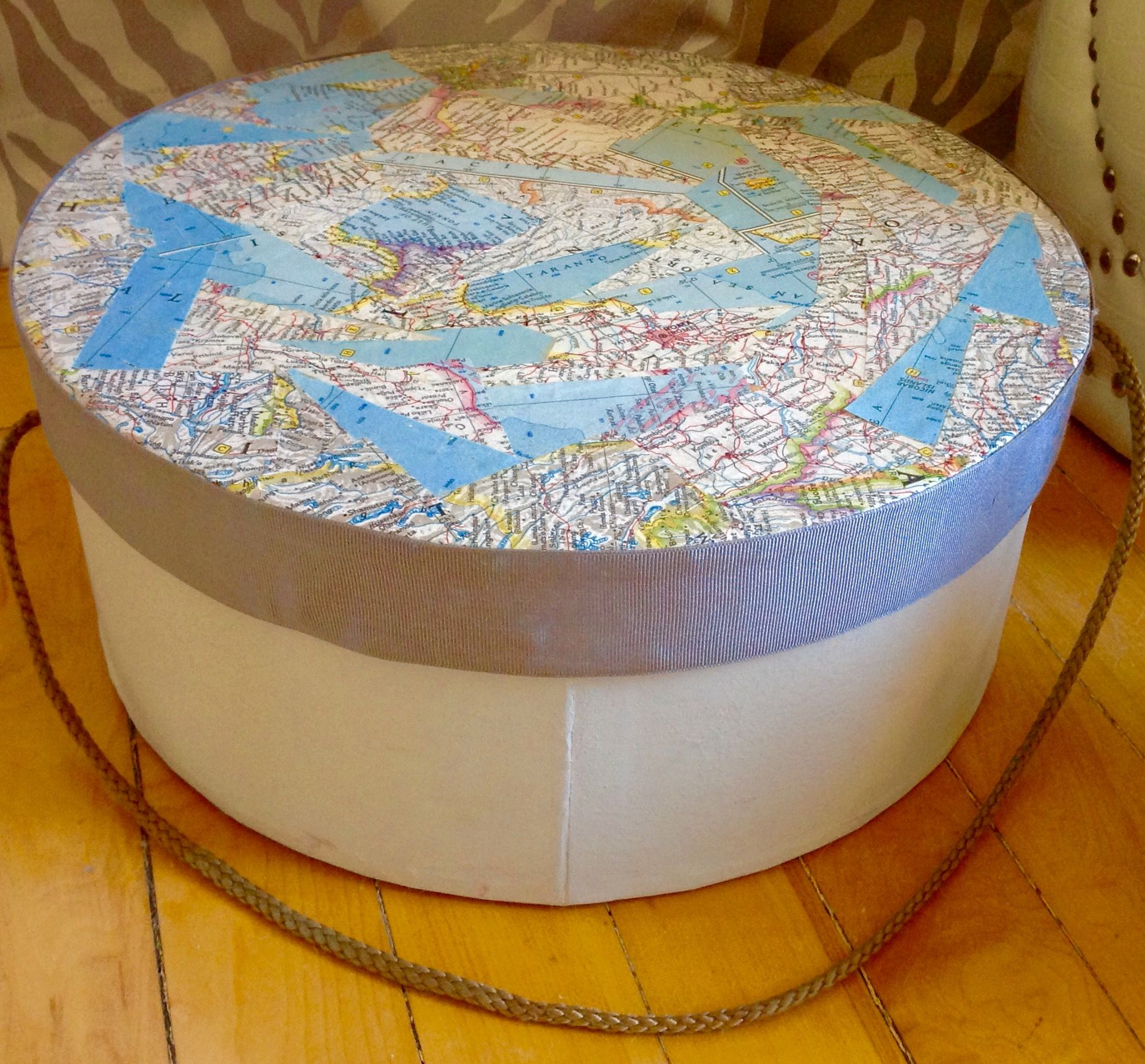 I had some nat geo map scraps leftover and an ugly 80's cardboard storage box. Painted the bottom with leftover wall paint from the room it lives in, mod pod he the scraps to the top and used the gray grosgrain from Target quilt packaging to cover the top side.