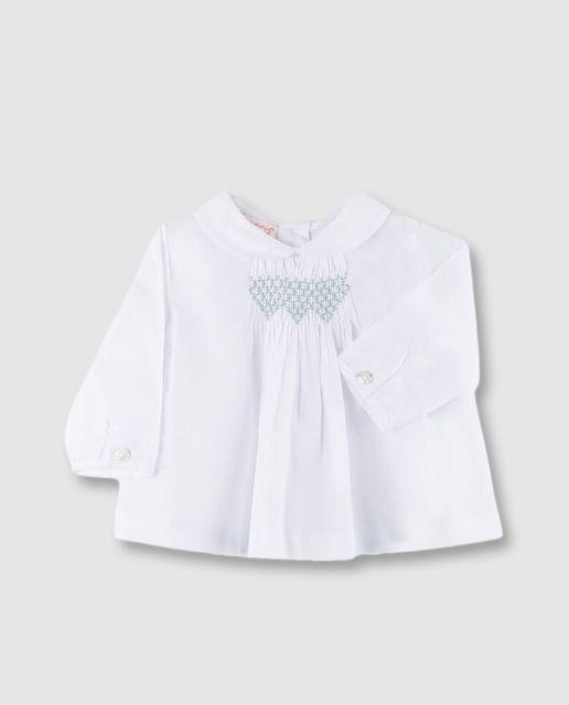 38ba91c0d Blusa en color blanco de manga larga y cuello bebé con jaretas y plisado en  el delantero. Tiene bordado a contraste y cierre con botones en al parte de  ...