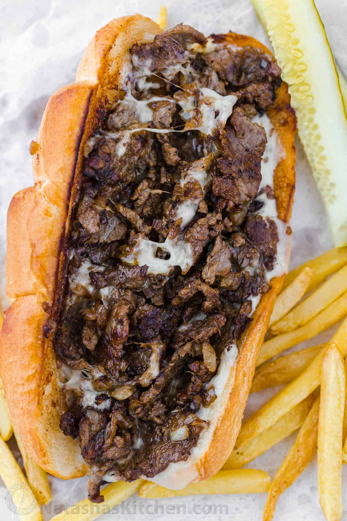 Philly Cheesesteak with tender ribeye steak, melted provolone, and caramelized onion in a garlic butter roll. Easy Philly Cheesesteak Sandwich video how-to.