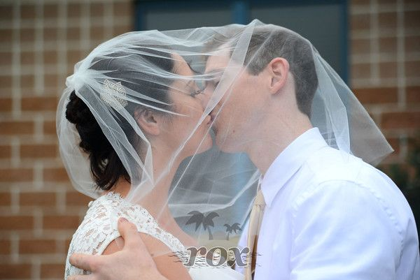 Bride and Groom kiss under wedding veil in Rehoboth, DE - image by Rox Photography:  https://www.roxbeachweddings.com/