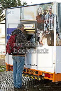 man is aan het pinnen bij de mobiele pinautomaat van de rabobank
