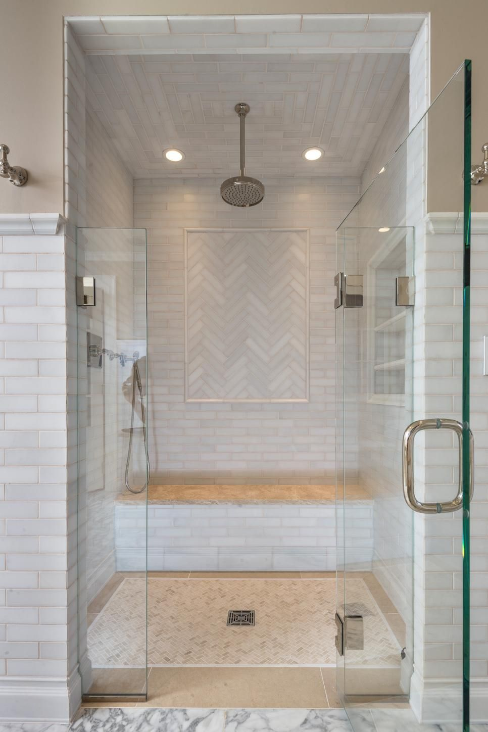The master bathroom for her features a beautiful walk-in shower with a top mounted head, a hand-held shower head, and built-in wall shelving and bench. The tiled interior and chevron patterns give it a touch of elegance and embellishment.