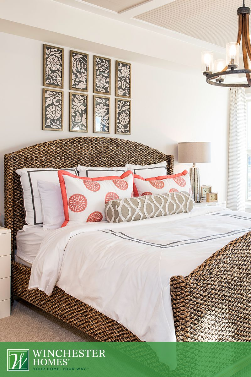 A wicker bed frame and wood chandelier make the master bedroom of ...