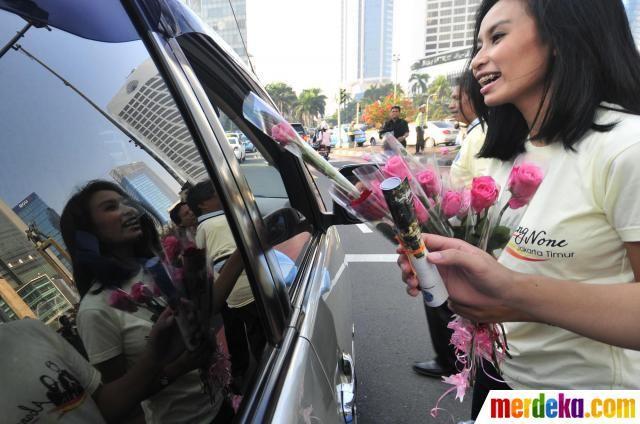 Para model membagikan bunga mawar merah kepada pengguna jalan di Bundaran HI dengan senyuman.