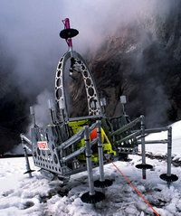 Photograph of a robot used to explore volcanic activity. It is built of metal plates and rods and it stands in the snow on legs that are loo...
