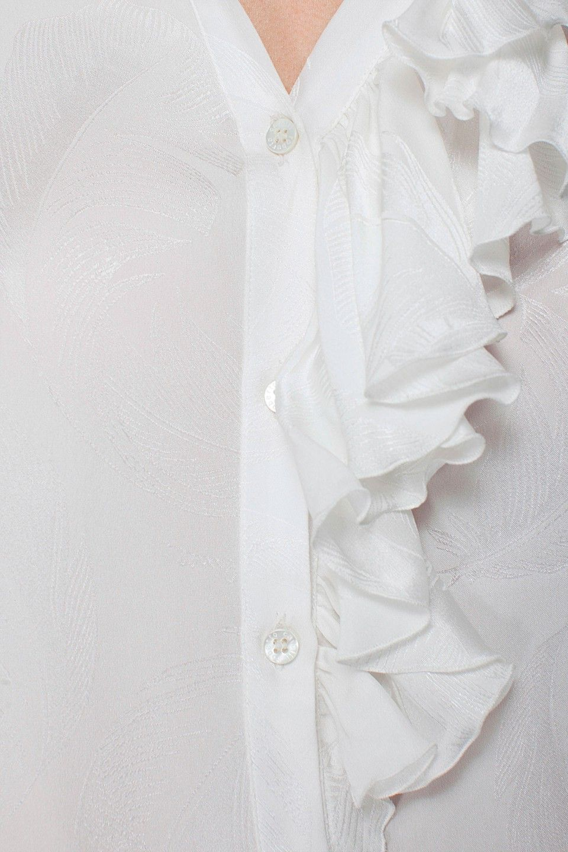 Camicia a maniche lunghe in crepe satin jacquard con fantasia a piume. Ampi jabot e bottoni in metallo dorato sulle maniche. 100% seta. Made in Italy. La modella veste una taglia 40 italiana, è alta 179cm e le sue misure sono 82cm - 61cm – 88cm.