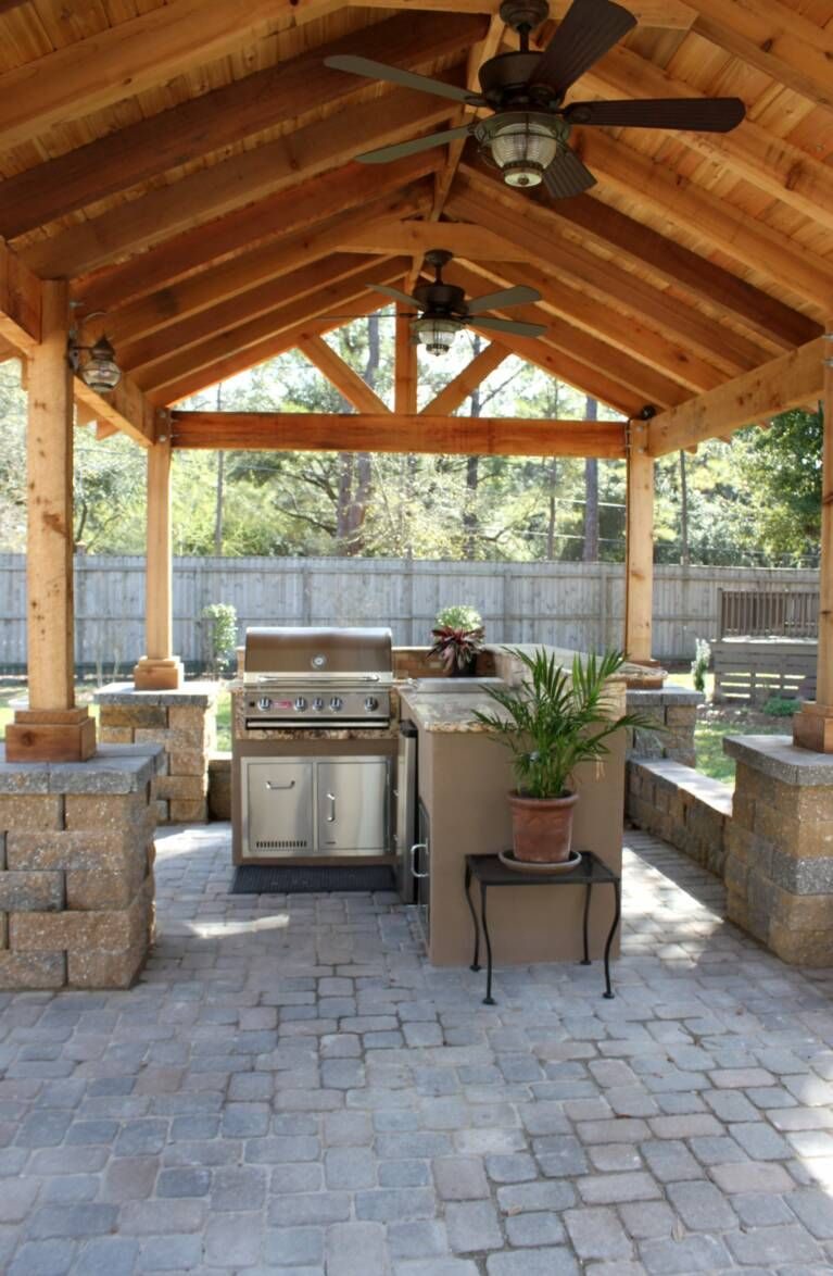 outdoor patio with peaked roof and fans except over a deck with lanterns instead of fans on outdoor kitchen ventilation id=79361