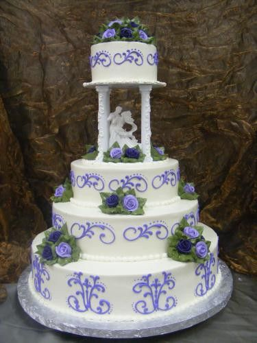 white buttercream frosting with purple open scroll with dots on all layers. Bouquet of buttercream roses in purple and eggplante with dark green leaves - on top