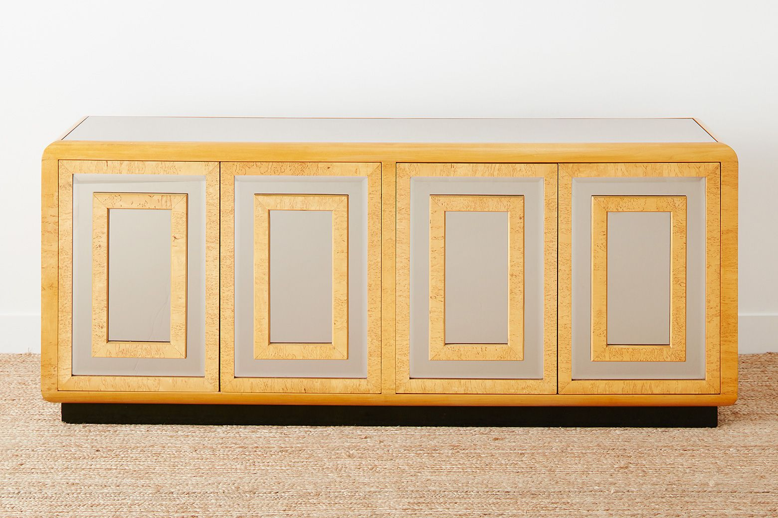 A low inspired low dresser with four mirrored doors, inset with burlwood. Behind each set of doors are three wooden drawers. This versatile piece could also be used as a credenza in a dining or living room.