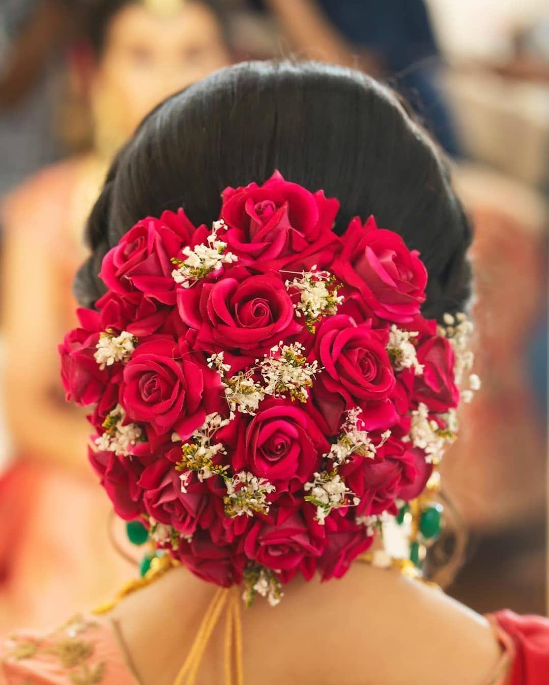 Big red rose floral bun bridal hairstyle indian wedding