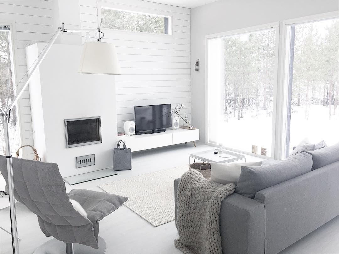 Valkoinen ja harmaa sisustus katsoo kohti ikkunoista avautuvaa luontomaisemaa. Sisustuksesta löytyy mm. Woodnotes K tuoli sekä Artemide valaisin, unohtamatta tietenkään upeaa valkoista takkaa.