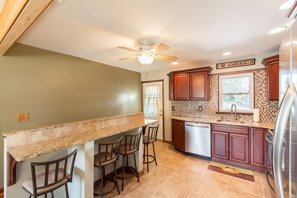 breakfast bar against a half wall in the kitchen granite