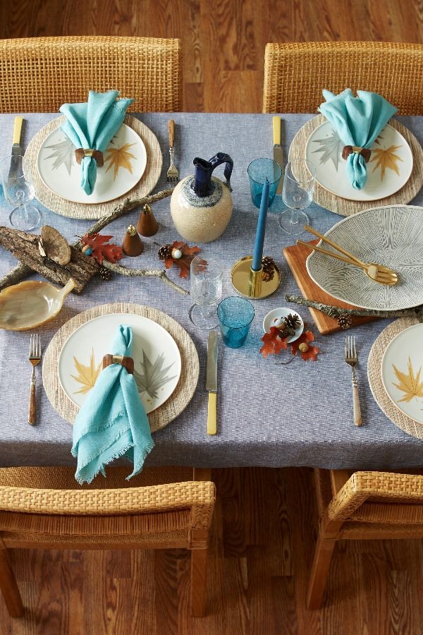 A blue tablecloth, napkins, glassware, and candlesticks carry a consistent color story without screaming fall, while leaf motifs on the plates and natural elements on the table nod to the season. - Photo: Adam Albright