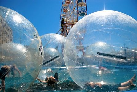 Children float in plastic bubbles at an amusement park in Cape Town, South Africa.<br>