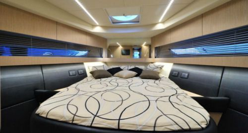 The master stateroom in the Austin Parker 42 Open is in the bow as it is on virtually every 42-footer. Note the cabinets over the long, large portlights and the artificial lighting on the overhead.