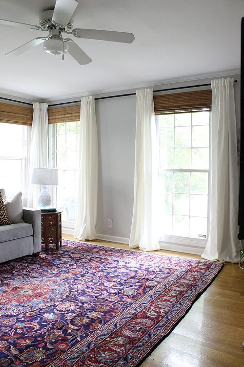 Captivating Large Colorful, Persian Rug Paired With White Curtains And Bamboo Shades  Styled By Claire Brody