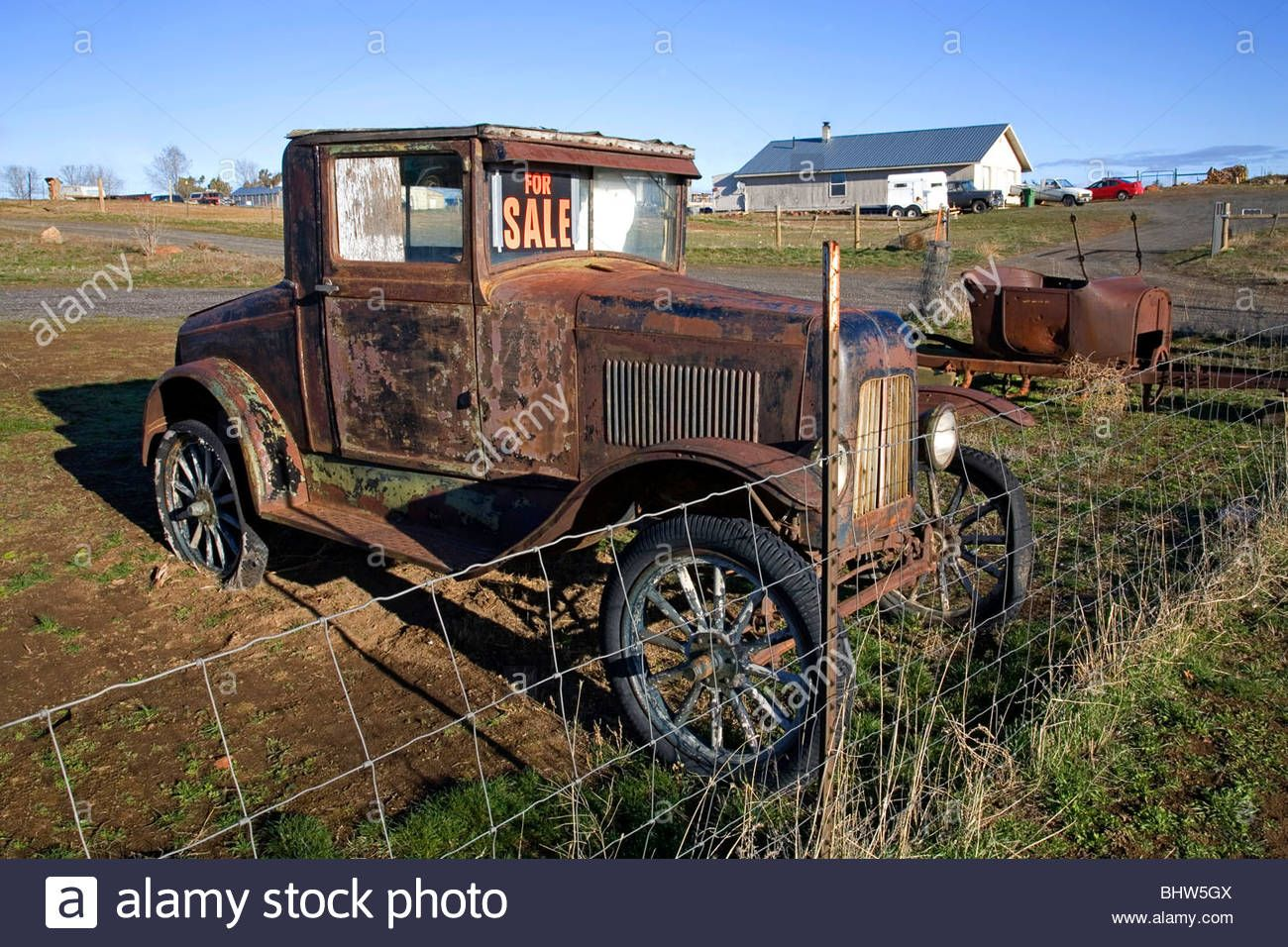 A For Sale sign on an ancient rusted classic car in a field near ...