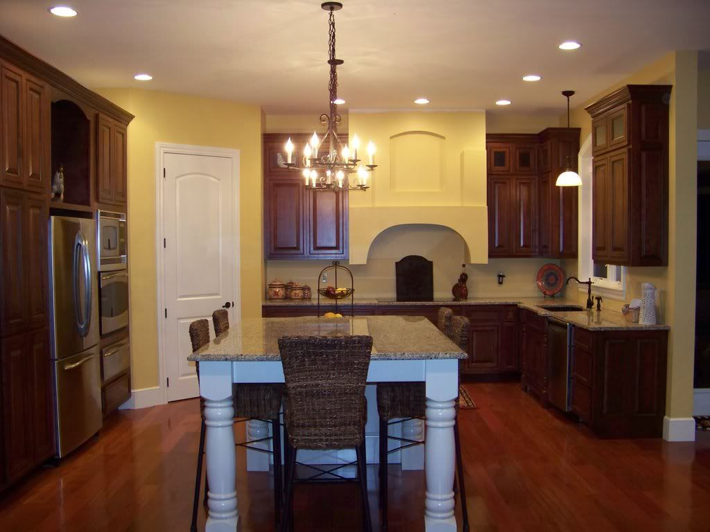 Dark Cabinets With Yellow Walls Breaking Up The Darkness Of