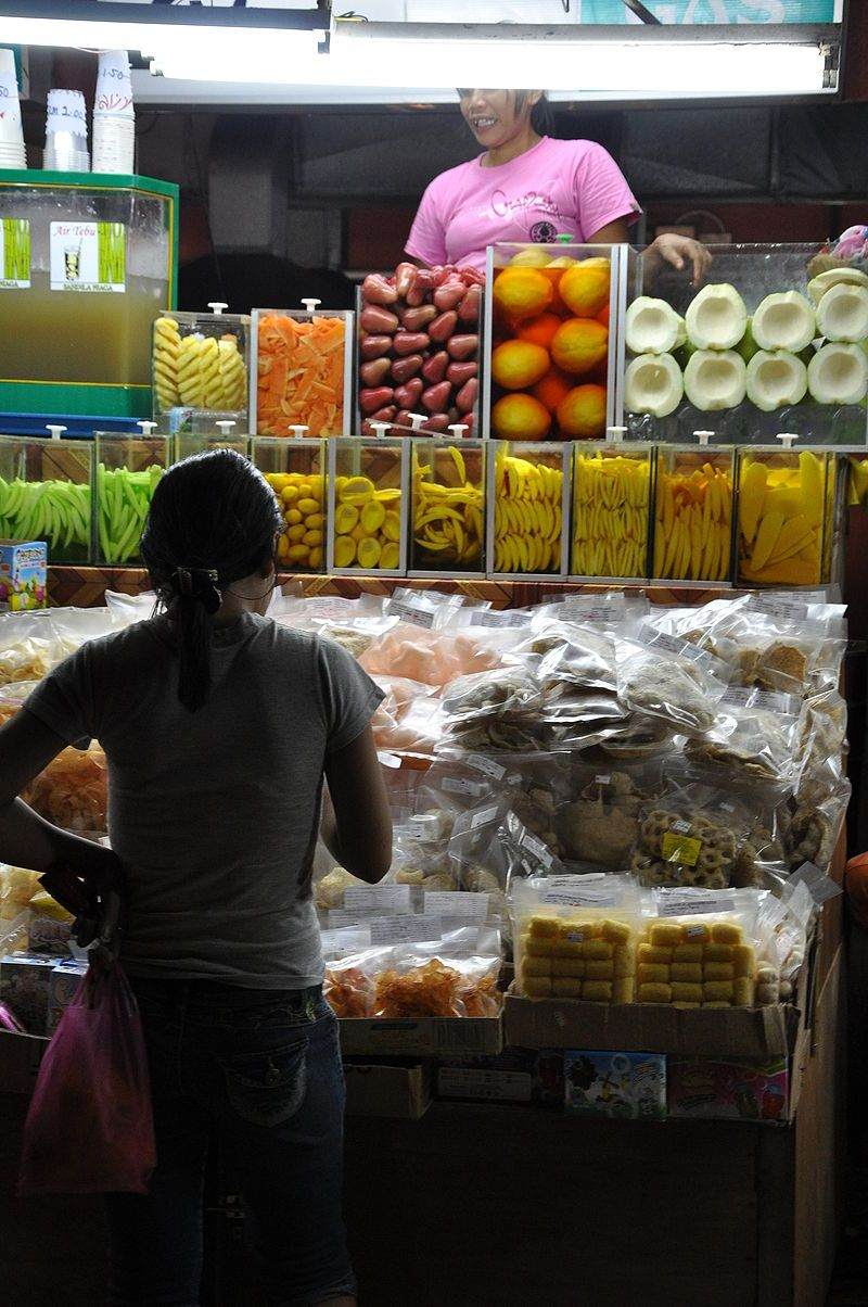 """Stall in the Tanjung Aru beach food hawker court selling """"ready to eat"""" fruit, dried fish and seafood snacks"""