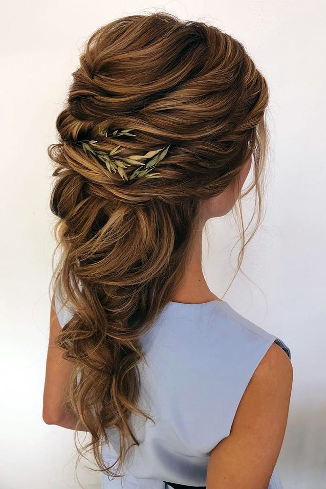 Boho loose wedding hairdo with greenery accents.