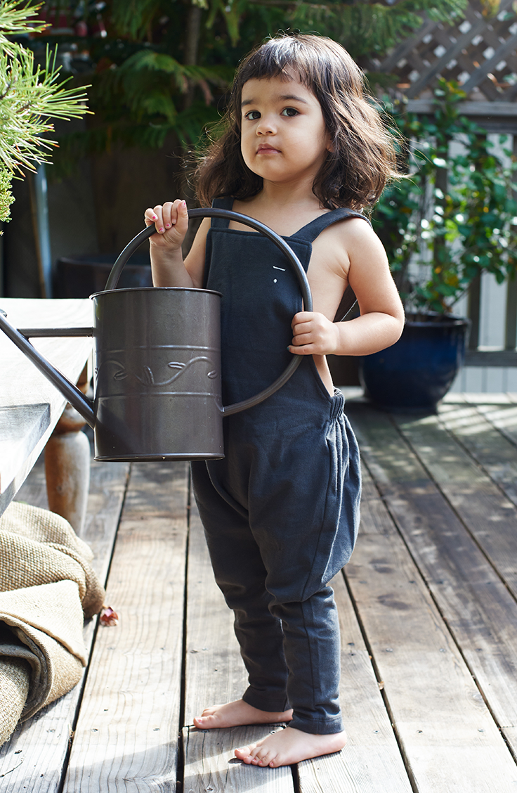 What Noble Carriage loves most about Amanda is that she makes living an organic life approachable, as you can see on her lifestyle blog, Raising Lila. She keeps so many beautiful green plants around her home and outdoors in the backyard garden. Here's her baby girl helping with the watering can, learning to grow and nurture. In her adorable gardening outfit from Noble Carriage by Gray Label, black salopette with adjustable straps made from organic cotton. Gorgeous thoughtful minimalist…