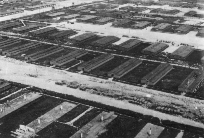 Reconnaissance photograph of the Majdanek concentration camp (June 24, 1944) from the collections of the Majdanek Museum, lower half: the barracks under deconstruction ahead of the Soviet offensive, with visible chimney stacks still standing and planks of wood piled up along the supply road; in the upper half, functioning barracks.