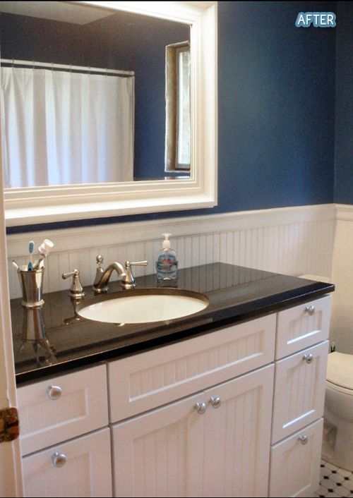 Bathroom blue walls huge mirror black counter on white cabinet