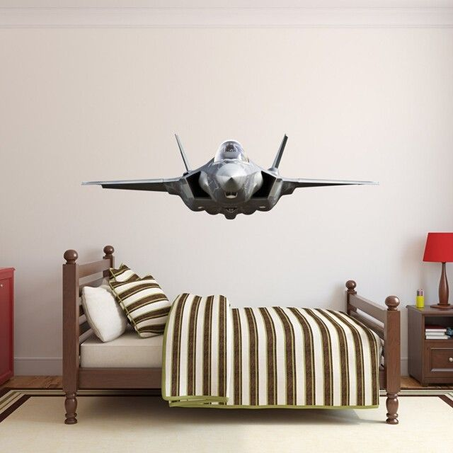 Large fighter jet wall decal with full, life-like colors on a beige wall above a bed in a children's room. The jet looks like it is flying towards whoever is looking at it and features a real life level of detail.