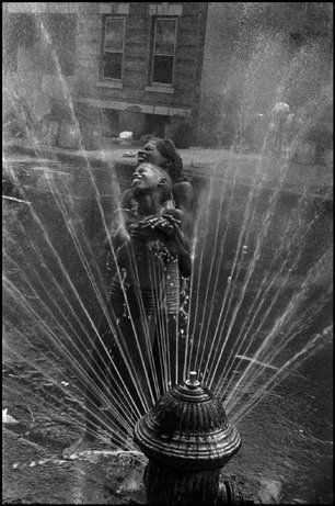A fire hydrant in Harlem opened during the summer heat. New York, 1963 | photo by Leonard Freed