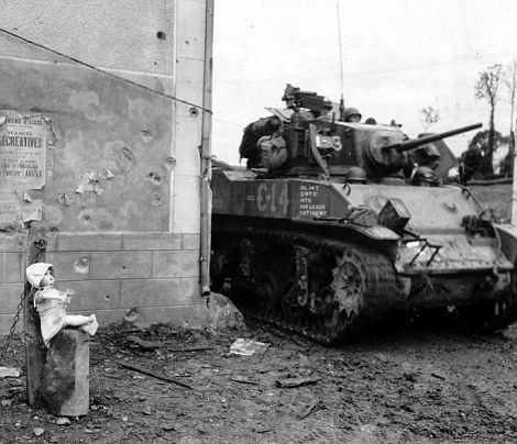 A doll posed against the concrete post as an enormous American M5A1 tank from the 3rd Armored Division drives past.