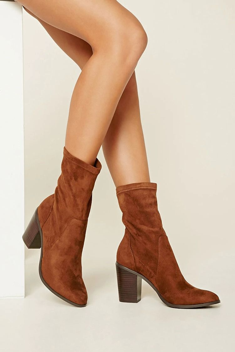 4fda322f4169 A pair of faux suede ankle booties featuring a faux wood block heel and a  slightly pointed toe.