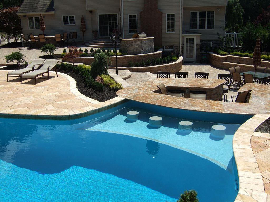 Beautiful pool with integrated outdoor kitchen bar stools for Pool design inc bordentown nj