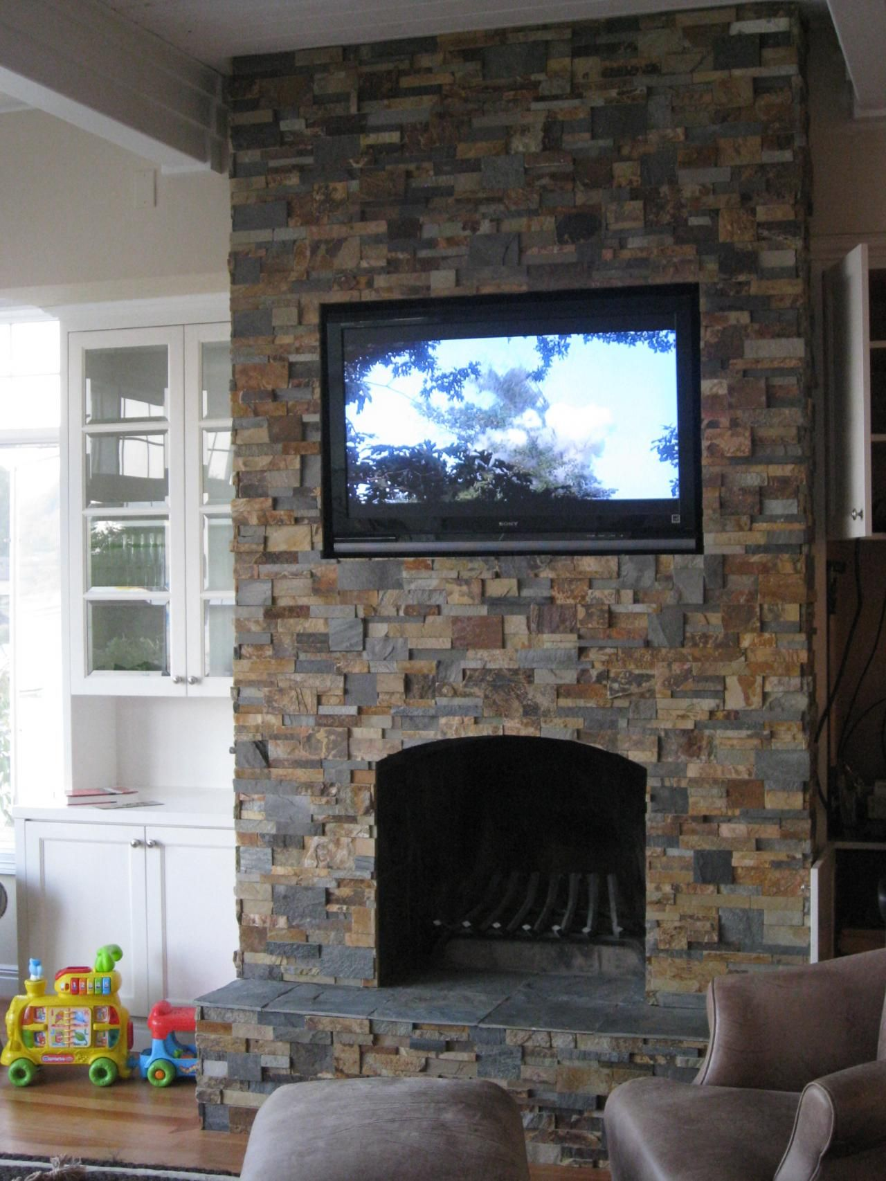 Custom framed stack stone toys stone fireplace for Tv over fireplace