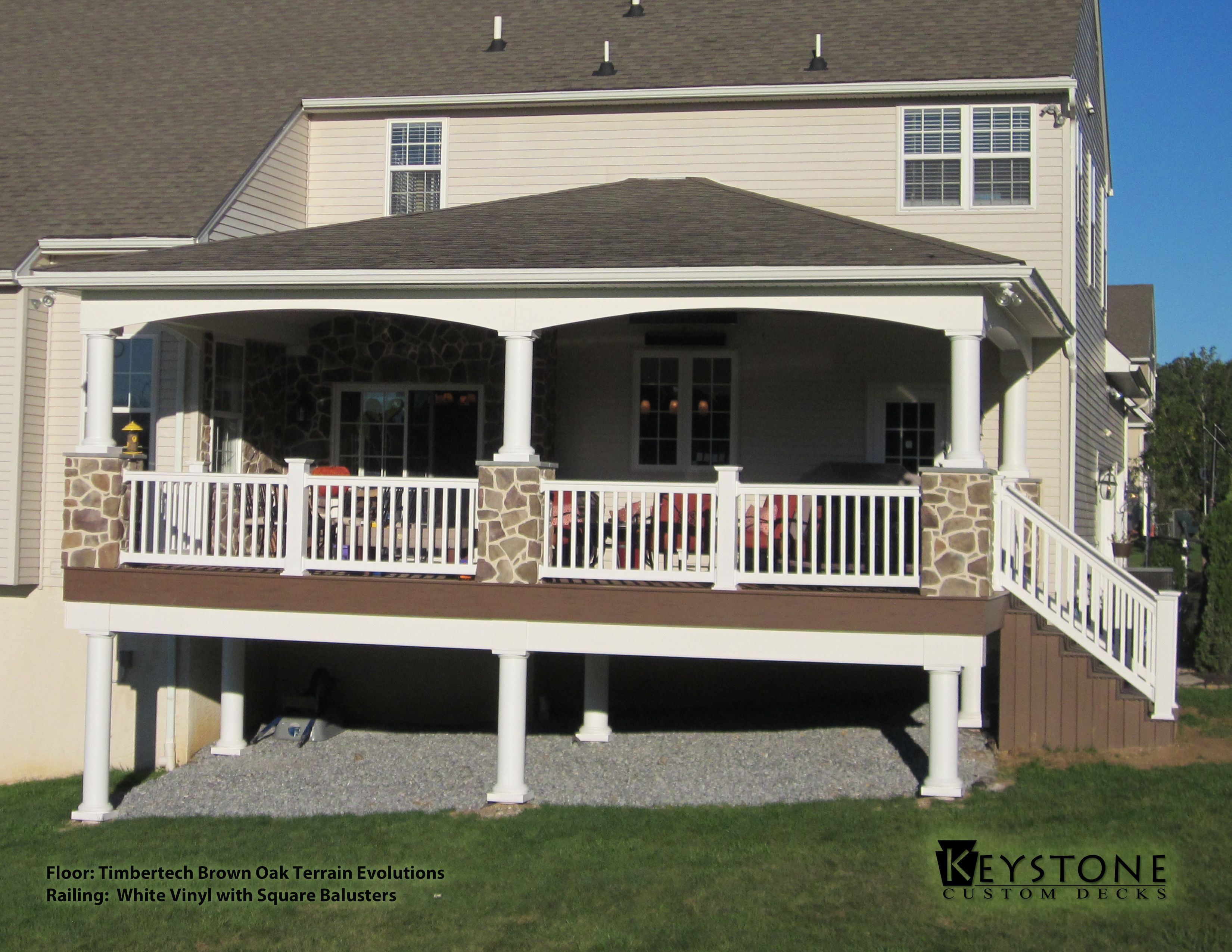 Timbertech brown oak evolutions with white vinyl railings and timbertech brown oak terrain evolutions decking and white vinyl railing and porch posts with square aluminum balusters also featuring custom stone work and baanklon Image collections