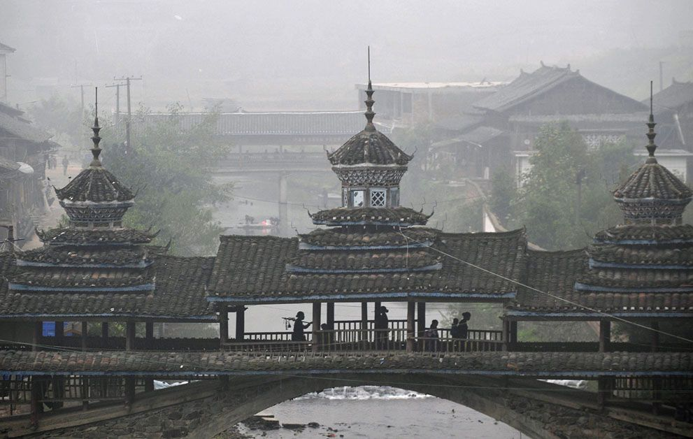 """""""Ethnic Dong minority villagers walk through a covered bridge on their way to a Kam Grand Choir gathering in Tongguan village of Liping county, Guizhou province, China. (photo by Sheng Li for Reuters)"""