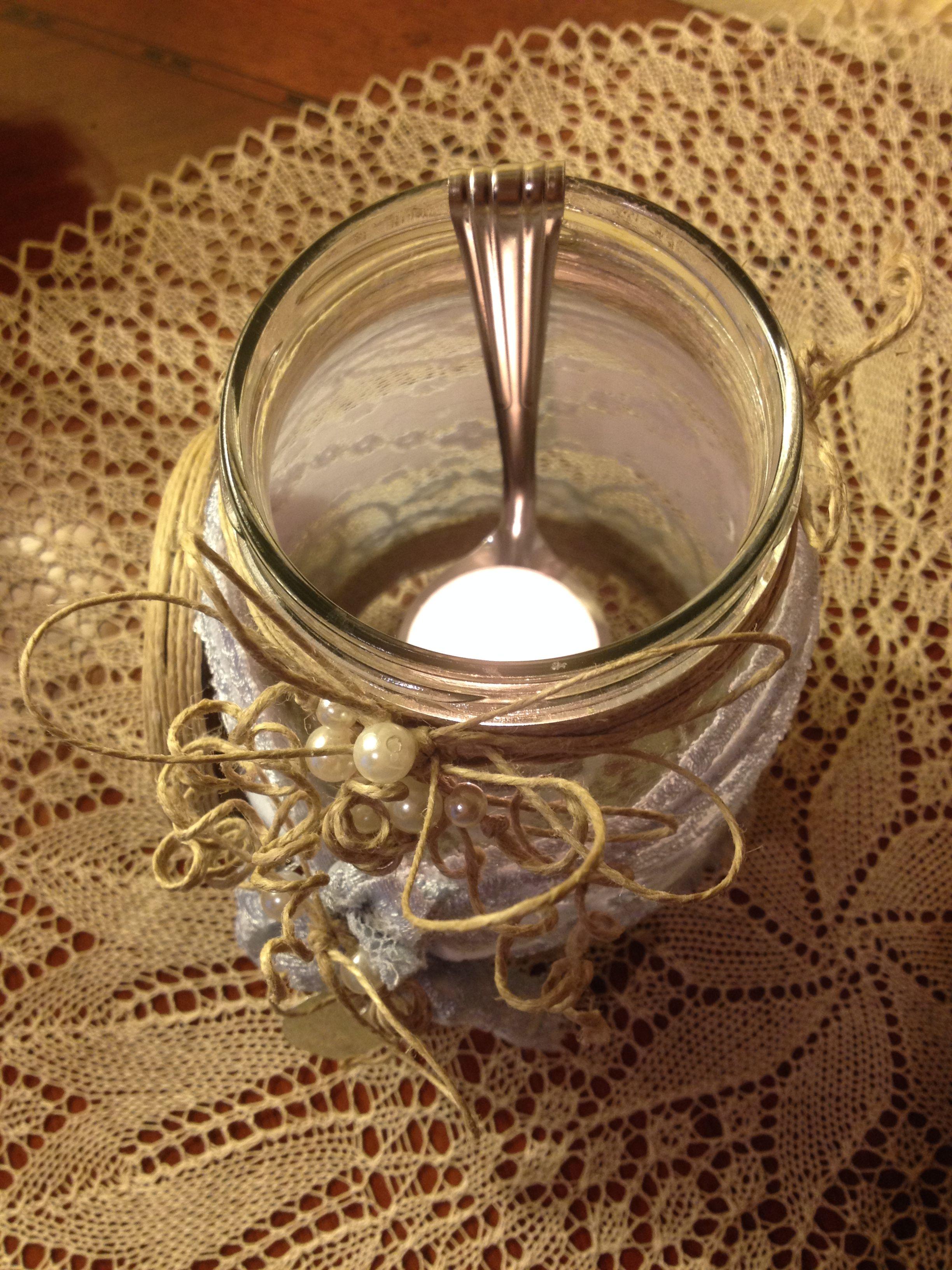 Artista Monica Bonaventura. Particolare di un porta candele realizzato con il riciclo di un vaso di olive abbellito con altro materiale di recupero. Il cucchiaio è stato anche questo riciclato e piegato per sorreggere il lumino