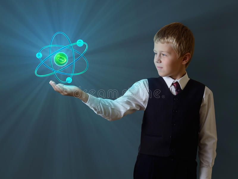 Schoolboy holding glowing atom Glowing atom of the child hand