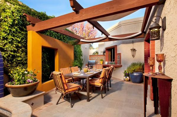 A colorful and enjoyable dining patio that has a movable shade fabric patio cover. www.findinghomesinhenderson.com #realestate #lasvegas #kellerwilliams