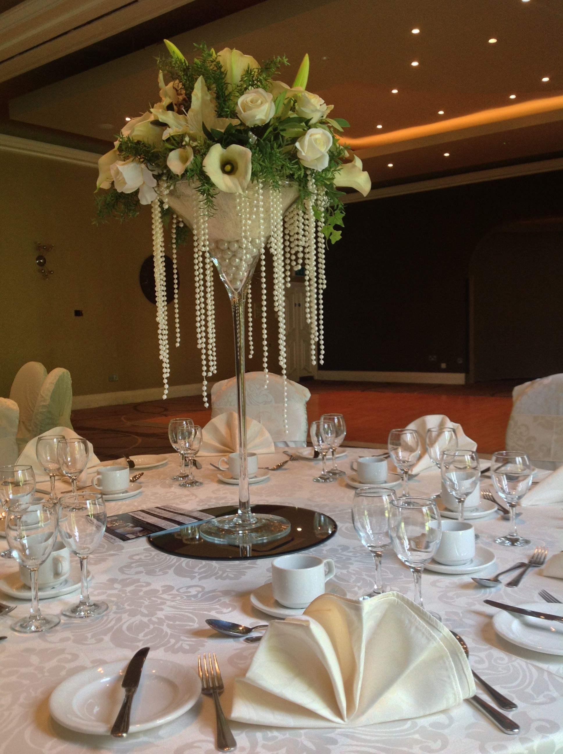 martini glass arrangement white rose and lily flowers set on gel pearls with pearl swag. Black Bedroom Furniture Sets. Home Design Ideas