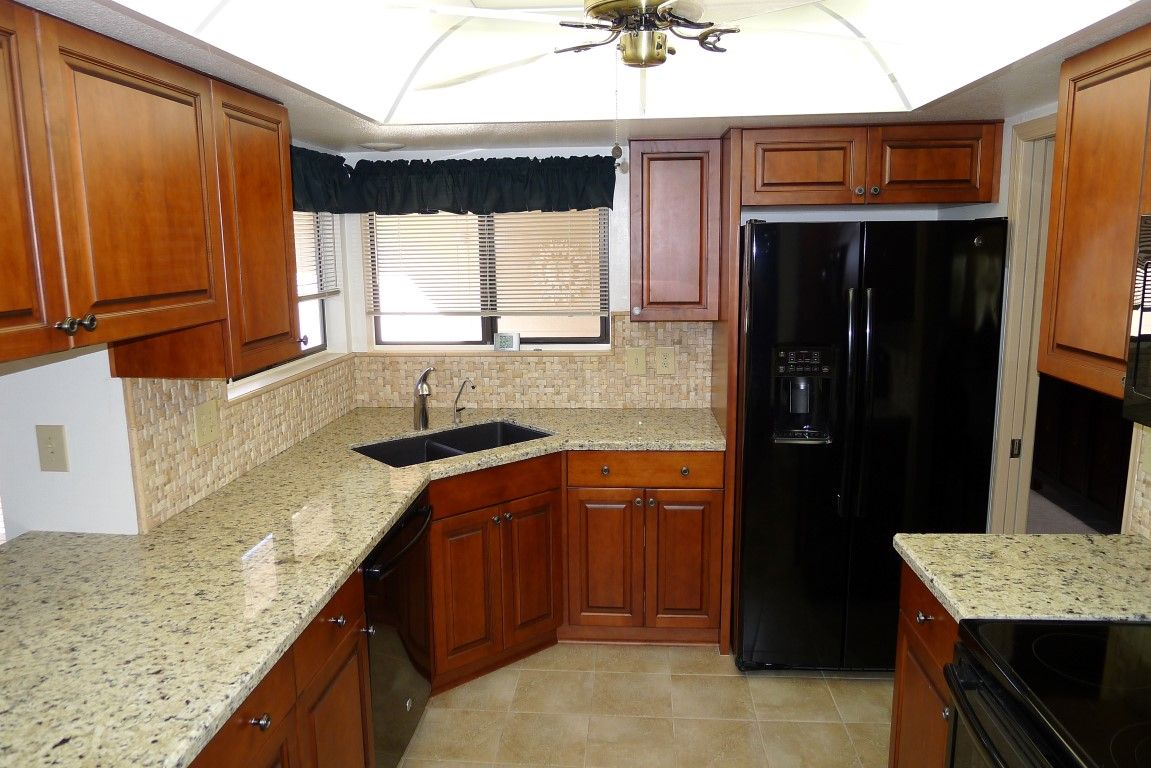 Maple Ultracraft Cabinets In Fairlawn Door Style With A Briarwood Stain With Brown Glaze Blanco 50 50 Granite Composite Under Mou Briarwood Tile Floor Cabinet