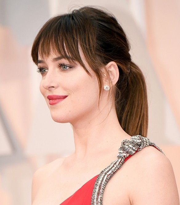 Dakota Johnson kept her look simple but super chic with a pony tail and red lips at the 87th Oscars