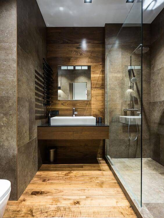 walk in shower in a luxury bathroom with stone tile and wood