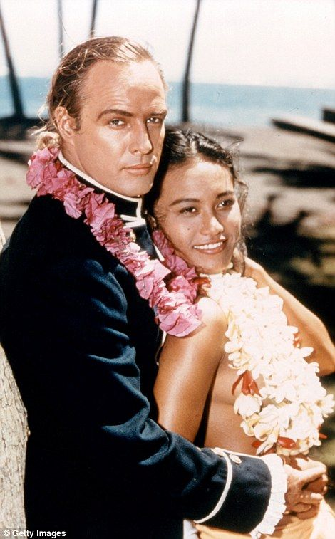 Marlon (left) is pictured in a military uniform holding onto Tarita in a scene from the film 'Mutiny on the Bounty', 1962