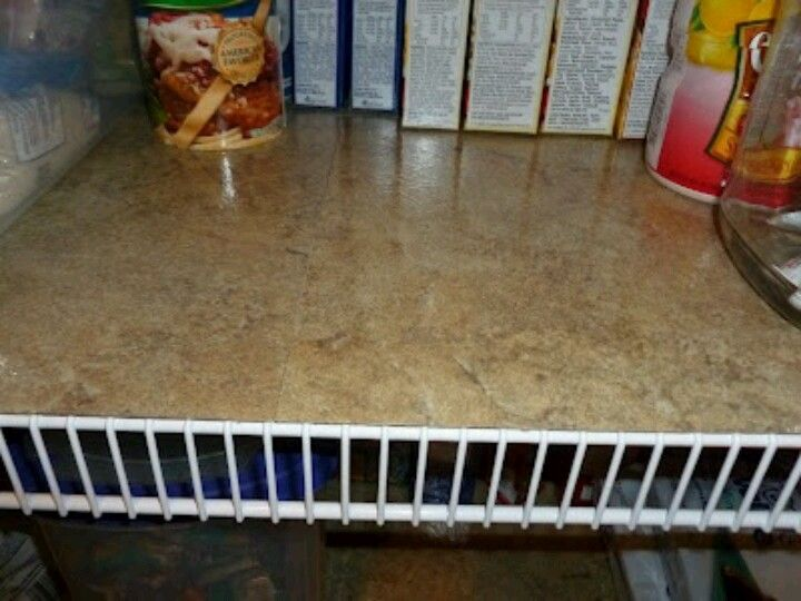 Shelf liner...I bought vinyl tiles at Home Depot, just peel the paper off the back and stick them to the shelves... they are easy to trim with kitchen scissors also...