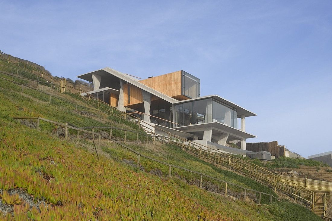 The Ghat House Sits On A Steep Slope Overlooking The Picturesque Pacific Ocean Ocean House Houses On Slopes Sloping Lot House Plan