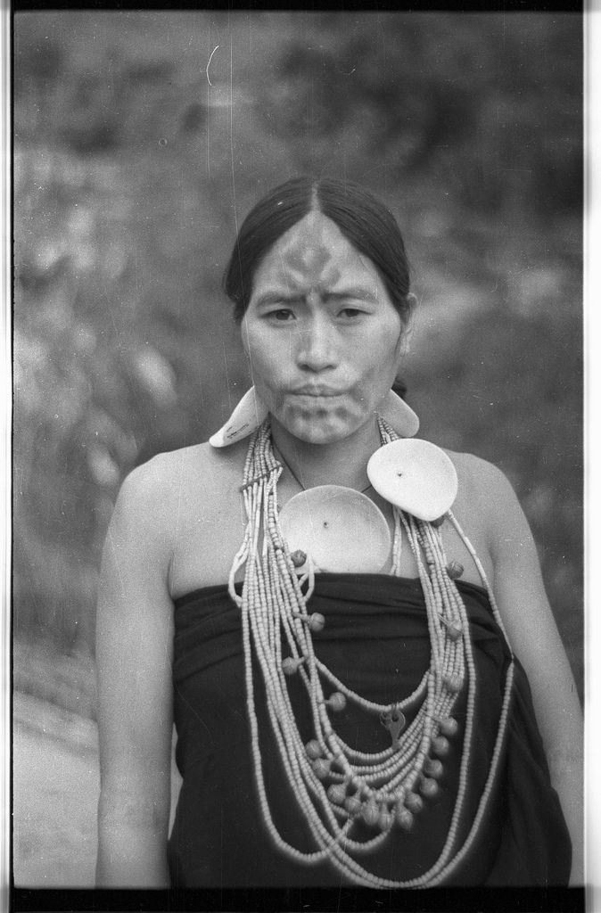 Chingmak's second wife, with face tattoo, wearing necklace of large shells | par SOAS Digital Library