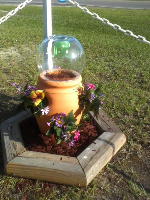 "This is my new ""pretty"" in my yard...I took a strawberry pot, a glass bowl with a solar light glued into it and some flowers and put it all together and yep...I am happy!"