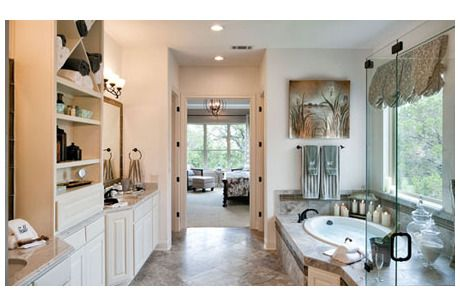 Built-in storage separates the sinks in this master bath. Tree-lined windows bring the outdoors in. The Vallagio by Toll Brothers in The Dominion - Andalucia community. San Antonio, TX.